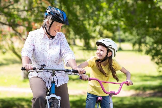 彼女の孫娘が自転車に乗っているおばあちゃん Premium写真