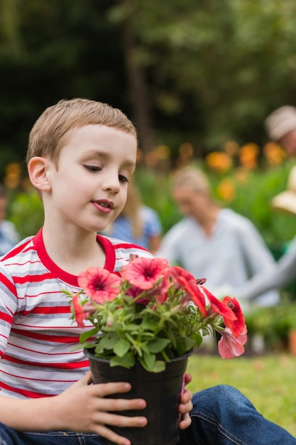 花の鍋で座っている若い男の子 Premium写真