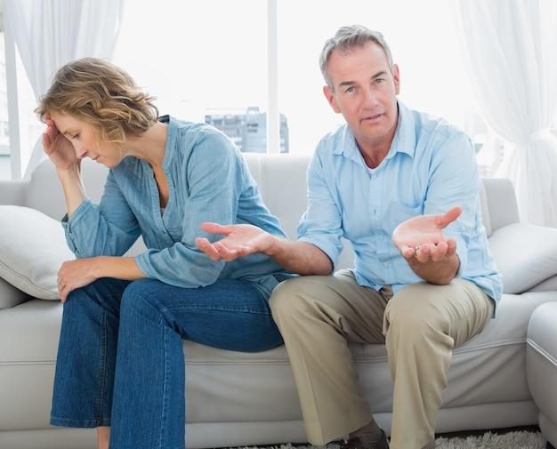 身に着けている男とソファに座っている中年のカップルを信じて Premium写真