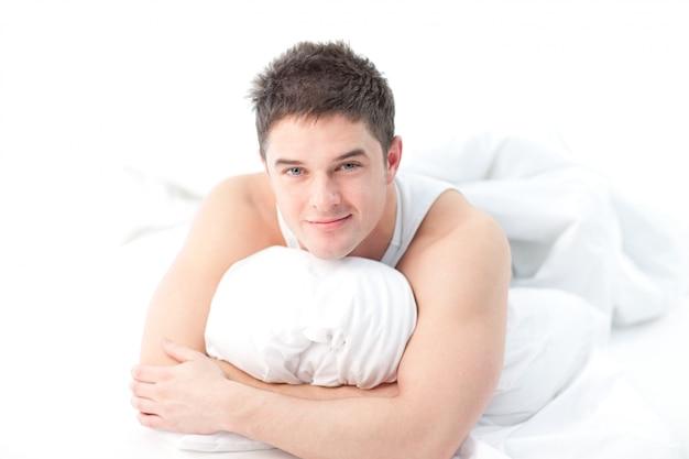 ベッドに横たわっている男は起きている Premium写真