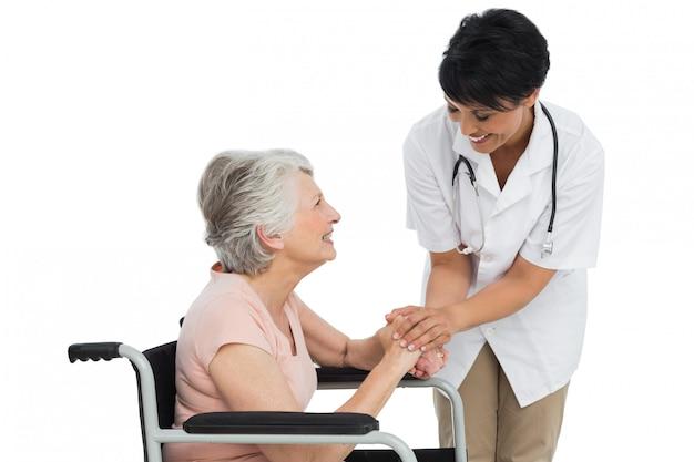 車椅子で上級の患者と話す女性医者 Premium写真