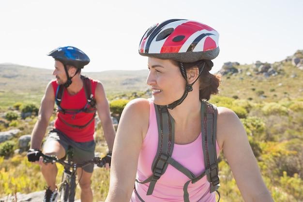 山トレイルで一緒に笑ってフィットするサイクリストカップル Premium写真