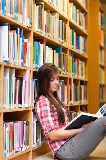 Портрет молодой женщины, читающей книгу Premium Фотографии