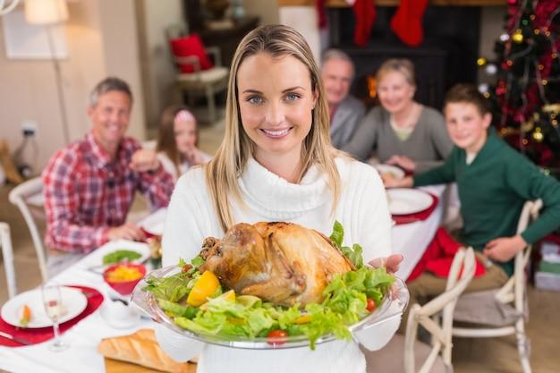彼女の家族の前で七面鳥を見せてくれる美しい女性 Premium写真