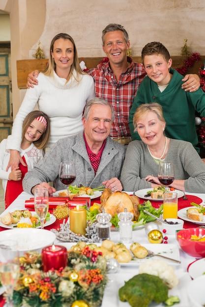 クリスマスの時間にカメラを見ている幸せな拡大家族 Premium写真