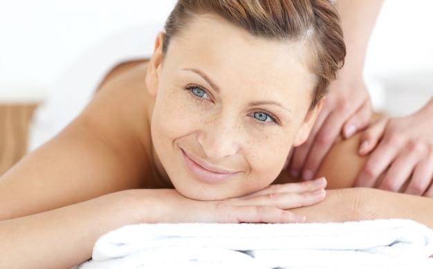 背中のマッサージを楽しむ笑顔の女性 Premium写真