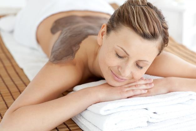 泥の皮膚治療を楽しむリラックスした女性 Premium写真