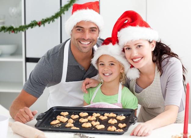 夫と娘とビスケットを準備している幸せな女性 Premium写真