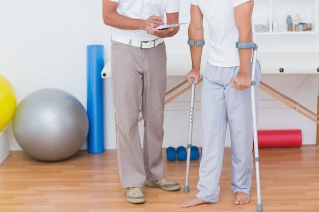 医者、松葉杖を持つ彼の患者にクリップボードを表示する Premium写真