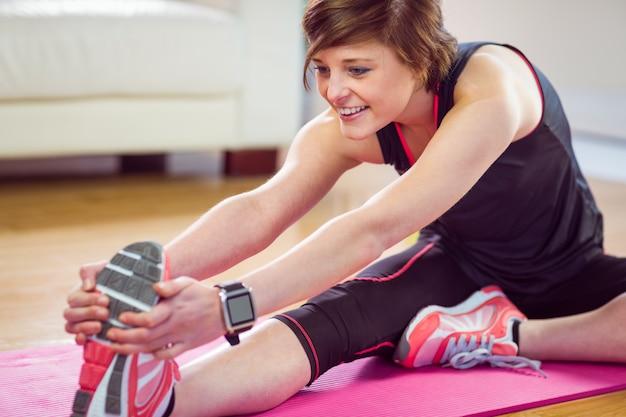 運動マットにストレッチする女性にフィット Premium写真