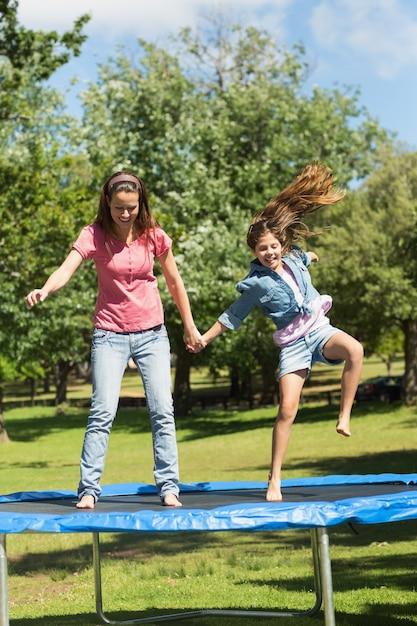 Счастливая девушка и мать прыгают высоко на батуте в парке Premium Фотографии