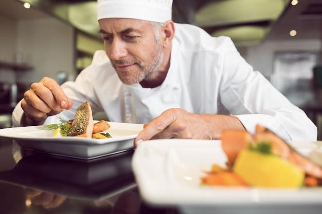 キッチン、料理を飾る集中的な男性のシェフ Premium写真