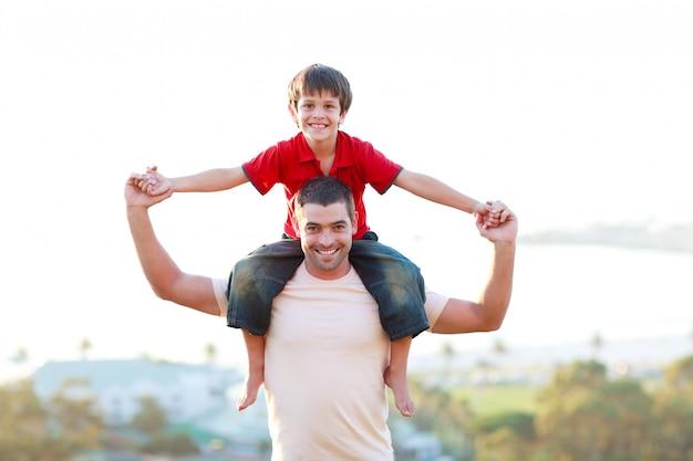息子ピギーバックライドを与える父 Premium写真