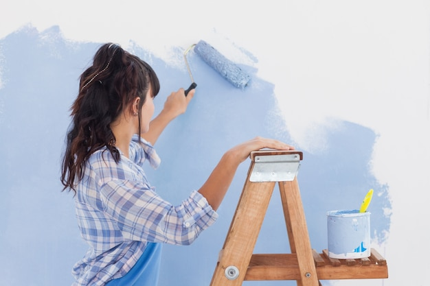 ペイント・ローラーを使って壁をペイントする女性 Premium写真