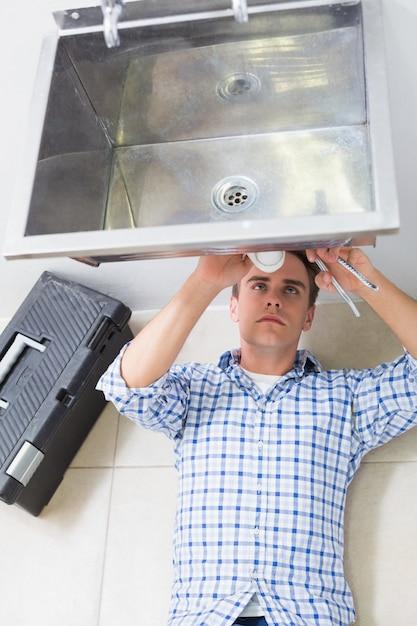 バスルームの洗面器の排水を修理する配管工 Premium写真