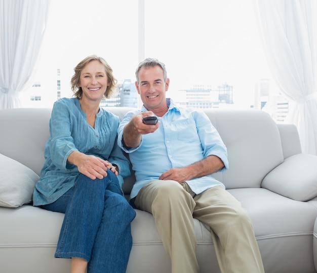 テレビを見てソファに座ってコンテンツの中年カップル Premium写真