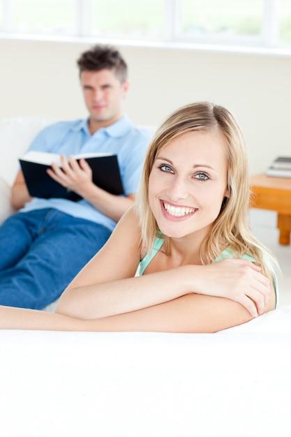 彼女のボーイフレンドがソファの本を読んでいる間、カメラで笑顔のガールフレンド Premium写真