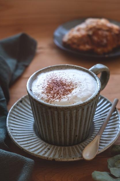 カプチーノコーヒーとクロワッサンの受け皿のマグカップ、木製の窓辺、窓からの光、クローズアップ Premium写真