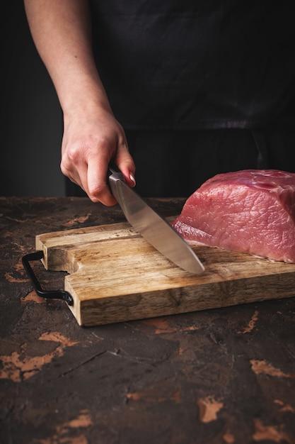 女性の手が台所で木の板に生豚肉をカット Premium写真