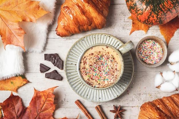 コーヒー、クロワッサン、カボチャ、白い背景に白いふわふわのセーター、カエデの紅葉。秋のコンセプト。 Premium写真