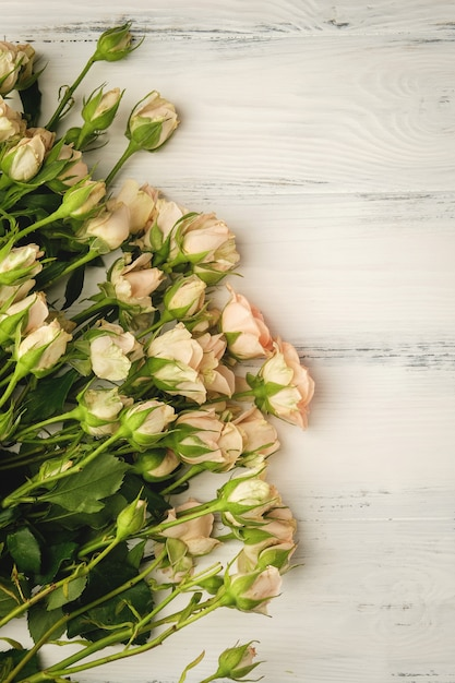 Букет из маленьких светло-розовых роз на белом деревянном столе, копия пространства Premium Фотографии