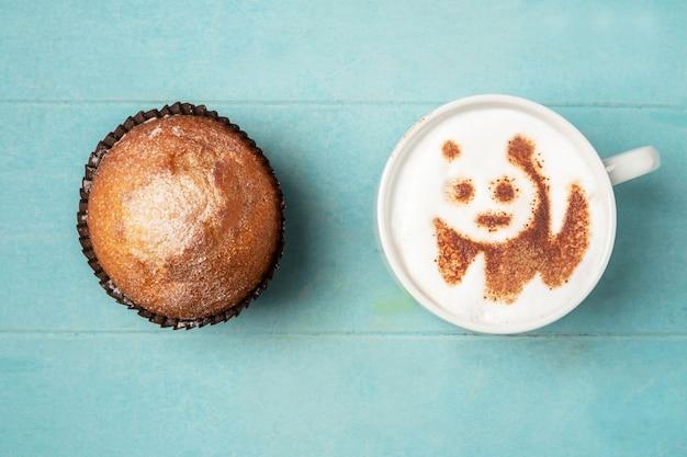 泡とカップケーキのパンダパターンとコーヒーの白いカップ、 Premium写真