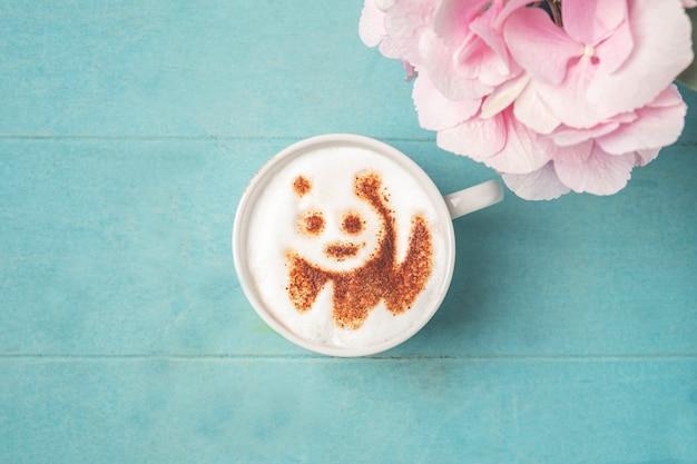 青い木製の表面の泡にパンダパターンとコーヒーの白いカップ、 Premium写真