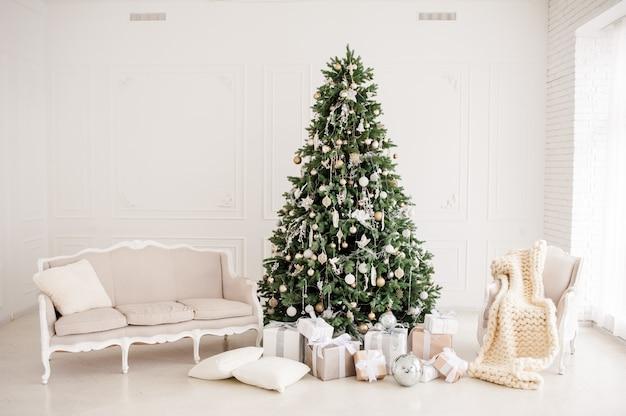 古典的なクリスマス新年はインテリアルーム新年ツリーを装飾されています。金の装飾とクリスマスツリー。モダンな白いクラシックスタイルのインテリアデザイン Premium写真