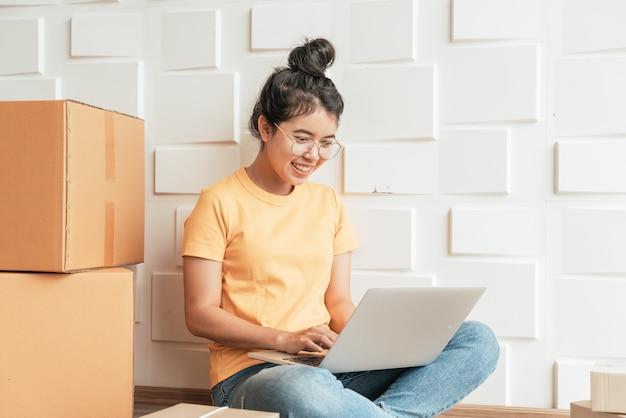 若いアジアのビジネスは、コンピューターを使用して電子メールまたはウェブサイトから顧客の注文をチェックし、パッケージを準備するためのオンライン販売者の所有者を立ち上げます Premium写真