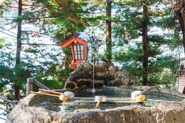 Водный пруд, традиция для мытья рук перед входом в храм в японии Premium Фотографии