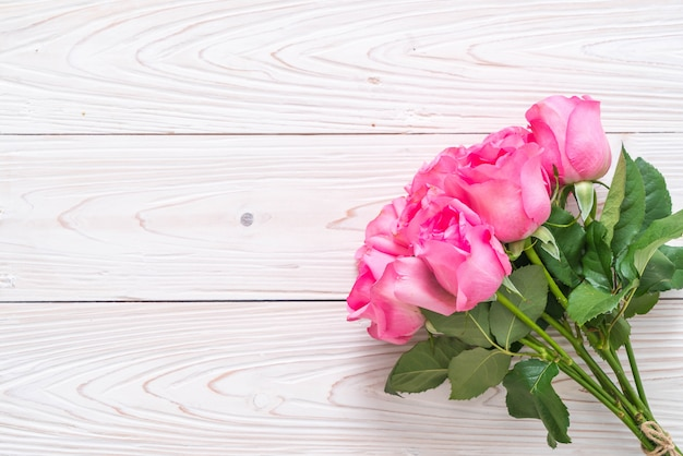 木製の背景の上に花瓶にピンクのバラ Premium写真