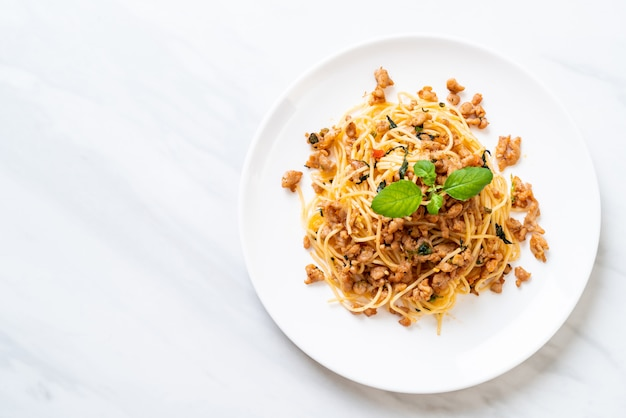 豚ひき肉とバジルの炒めスパゲッティをかき混ぜる Premium写真