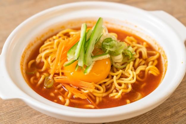卵、野菜、キムチ入り韓国の辛いインスタントラーメン Premium写真