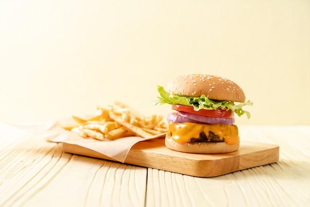 チーズとフライドポテトと新鮮なおいしい牛肉バーガー Premium写真