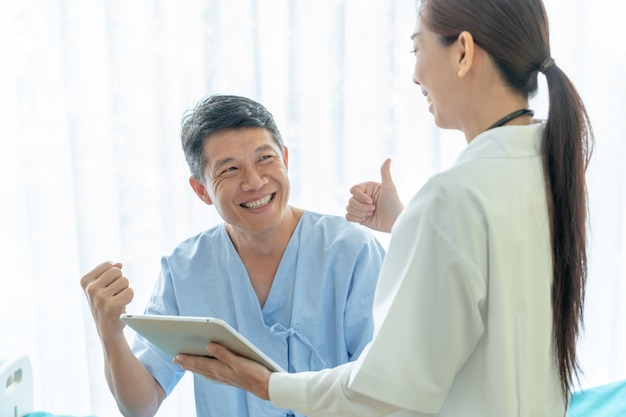 Азиатский старший пациент на больничной койке обсуждая с женским доктором Premium Фотографии