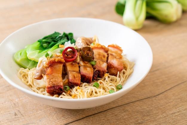 シャキッとした豚バラ肉とワンタンの卵麺スープ Premium写真