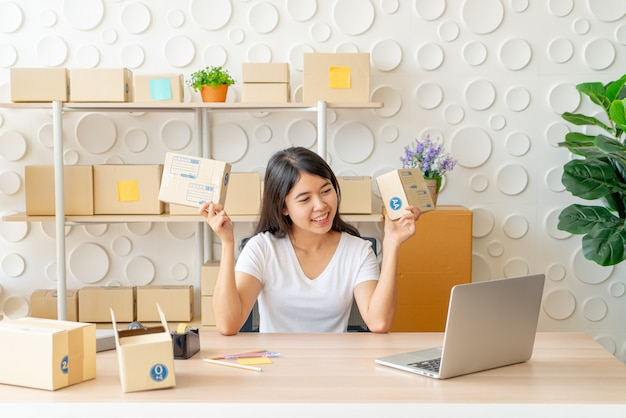 職場の梱包箱で自宅で働くアジアの女性ビジネスオーナー Premium写真