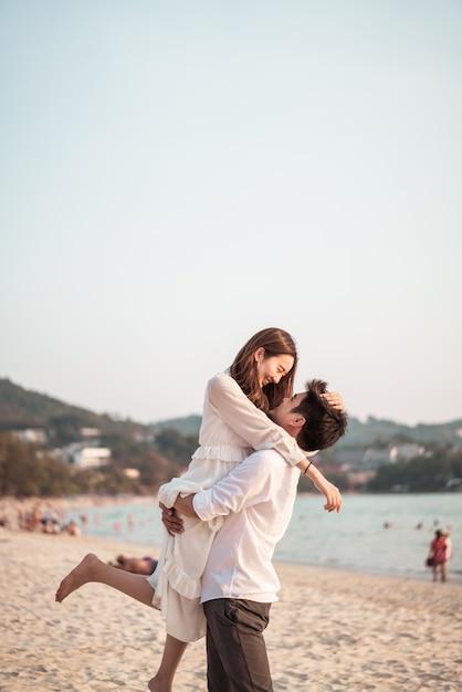 Счастливая пара собирается в свадебное путешествие на тропический песчаный пляж летом Premium Фотографии