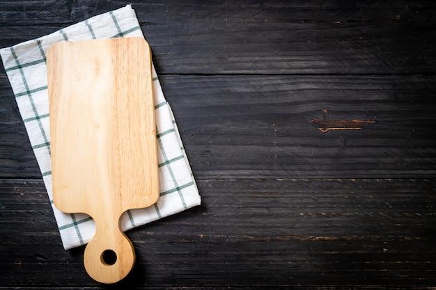 暗い背景に台所布で空の切断木の板 Premium写真