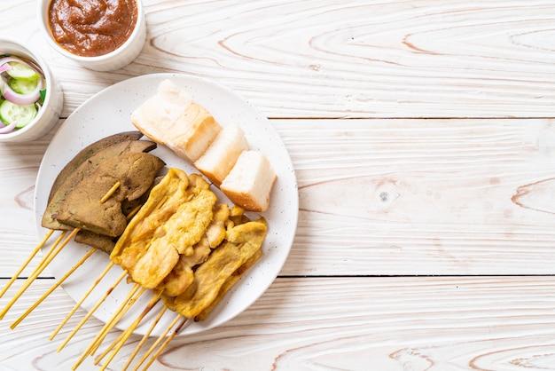 ピーナッツソースとキュウリのスライスと酢の玉ねぎのピクルスを添えたポークサテ Premium写真