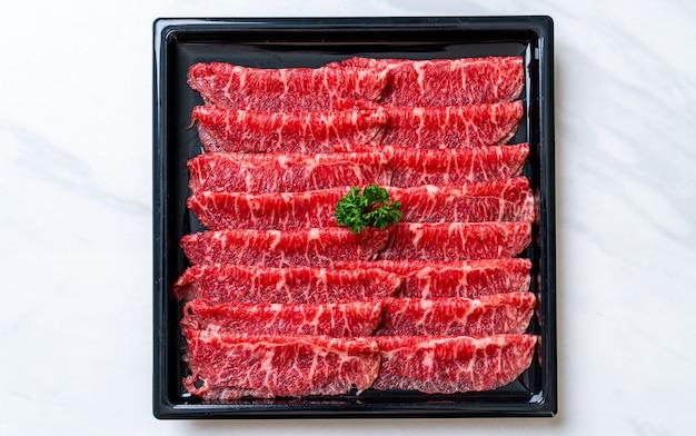 霜降りテクスチャでスライスした生の牛肉 Premium写真