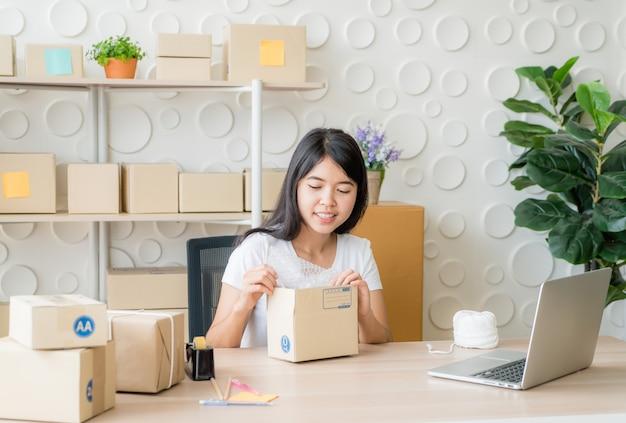 Азиатский владелец бизнеса женщины работая дома с коробкой упаковки на рабочем месте Premium Фотографии