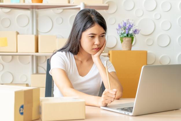 Молодая азиатская женщина запускает владельца малого бизнеса работая с цифровой таблеткой на рабочем месте. Premium Фотографии