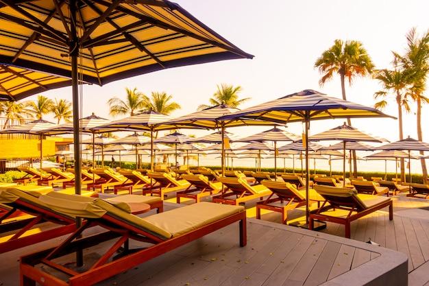 ホテルとリゾートの屋外スイミングプールの周りの美しい豪華な傘と椅子 Premium写真