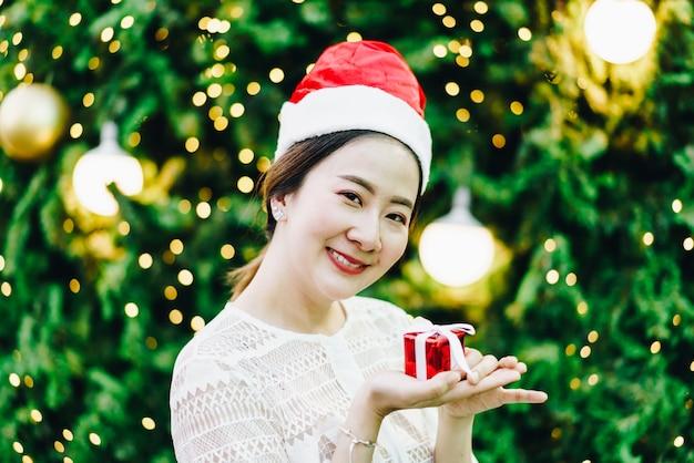お祝いクリスマスフェアのギフトを持つ笑顔の美しい若いアジア女性の肖像画 Premium写真
