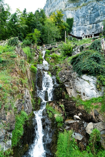 聖ビータス洞窟とスイス、サンドラウエネンのチューナー湖の上の滝。 Premium写真
