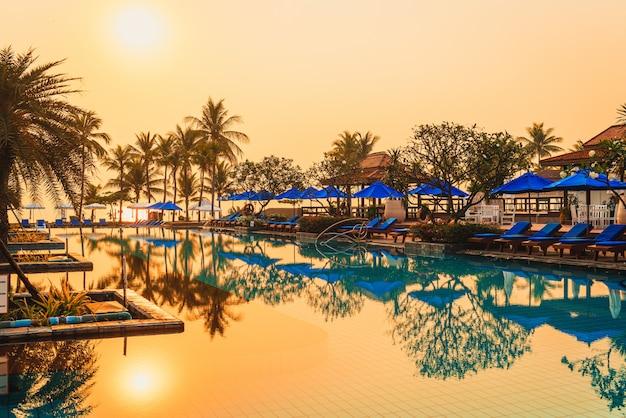 日の出時に高級ホテルリゾートの傘椅子プールとヤシの木 Premium写真