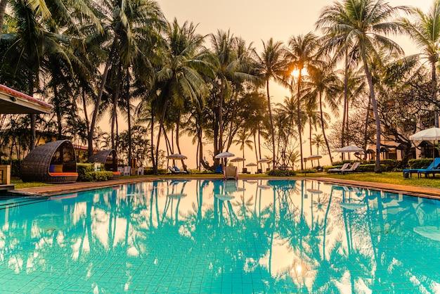 ホテルとリゾートのスイミングプールの周りの美しい傘と椅子 Premium写真