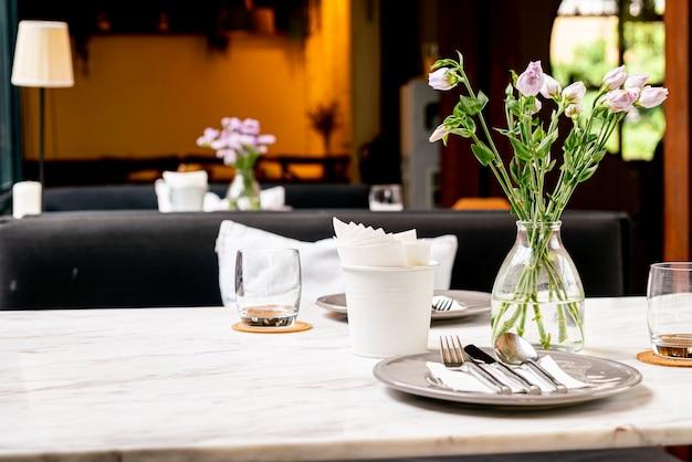 ダイニングテーブルの上に花瓶の美しい花 Premium写真
