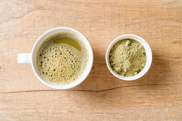 抹茶パウダーと泡だて器のホット抹茶グリーンティーカップ Premium写真